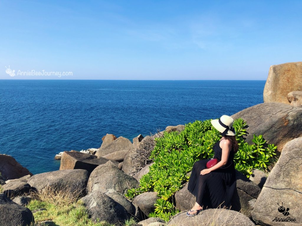 a girl sit at the rocky bank (Thao Nguyen) in Green island (Cu Lao Xanh) of Quy Nhon, Vietnam