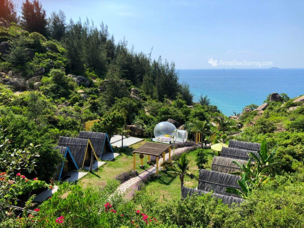 green forest with thatched bungalows next to the beach in Trung Luong camping site, Quy Nhon, Vietnam
