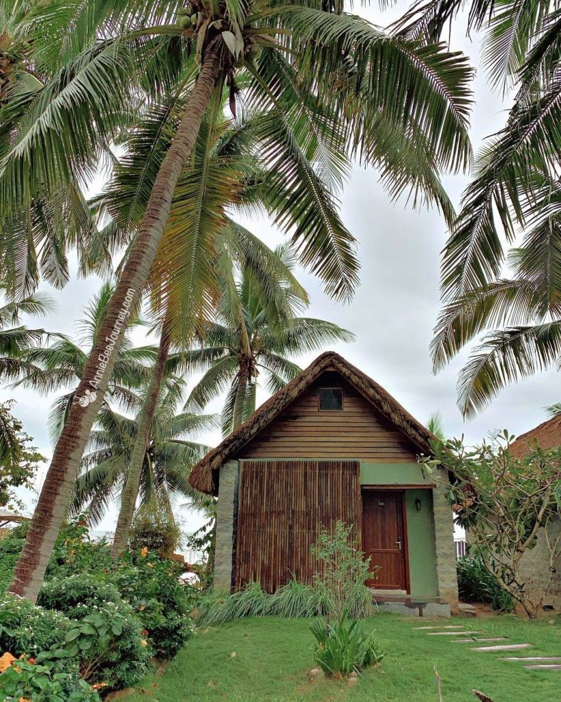 Thatched bungalows with coconut trees at Casa Marina resort Quy Nhon, Vietnam