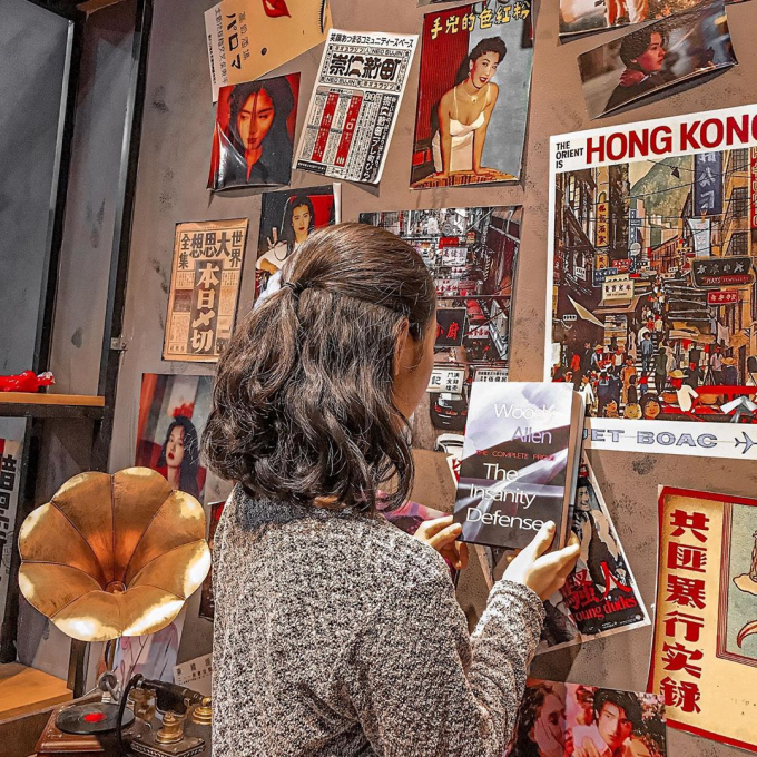 the girl standing in front of the wall hung Hong Kong magazine publications at Little Hong Kong coffee shop in Quy Nhon, Vietnam